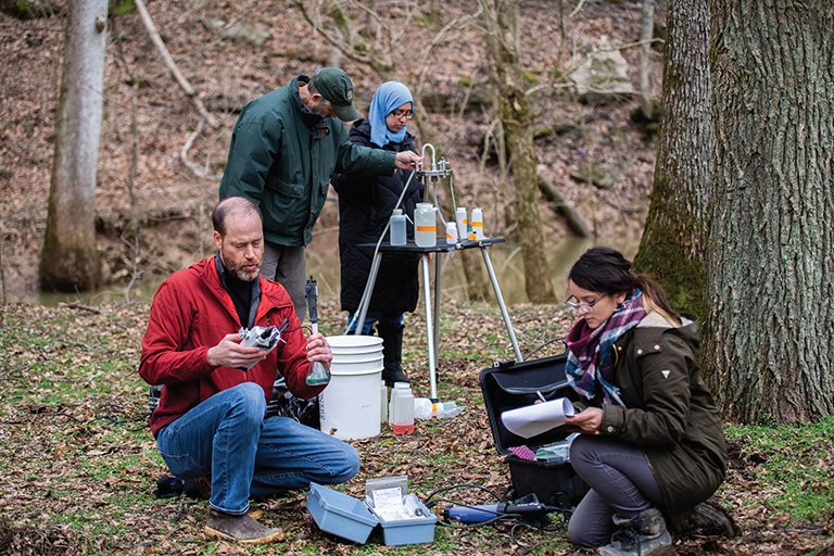 Two faculty members and two students gathered together to analyze water samples